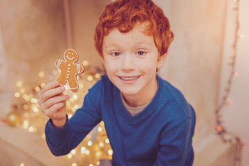 Favorite dessert. Charming red-haired man sitting near the chimney and showing a gingerbread man to the camera while smiling
