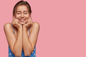 Photo of cheerful pleased model closes eyes with pleasure, dreams about something, has toothy smile, keeps both hands under chin, shows bare shoulders, isolated over pink background with free space