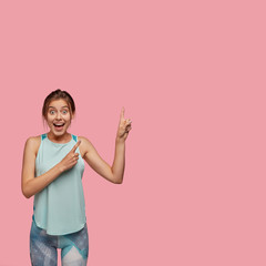 Content slim woman dressed in sportswear, stands on left side, indicates upwards, shows free space against pink background, being impressed by something positive. Advert, feminity, lifestyle