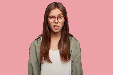 Indoor shot of indignant woman frowns face in displeasure, wears spectacles, shirt, models against pink background, doesnt like something dressed in casual shirt. Facial expressions concept.