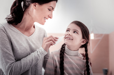 Caring about health. Portrait of smiling mother giving nasal drops to her daughter while the daughter smiling at her mother