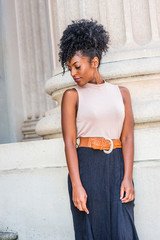 Young African American Girl with afro hairstyle, white ear bead pin, wearing sleeveless light color top, dark orange belt, black skirt, standing outside office building in New York, looking down..