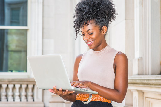 Way to Success. Young African American woman with afro hairstyle wearing sleeveless light color top, standing in vintage office building in New York, looking down, working on laptop computer, smiling