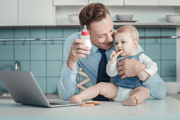 Do you want. Pleasant caring handsome father spending time in the kitchen with his children smiling and holding a bottle.