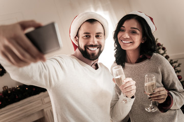 Happy people. Handsome bearded man keeping smile on his face and standing near his girlfriend while doing selfie