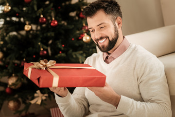 Festive mood. Delighted nice cheerful man smiling and unpacking the present while being in a festive mood