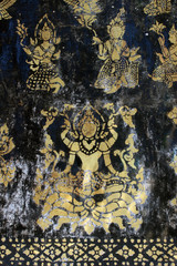 Elements from an ancient aged decoration of gods or goddesses painted in gold on black on a wall at a Buddhist temple in south east Asia.