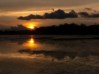 silhouette sunset on a beautiful Krabi Thailand beach. gold color sky sunset soft smooth sand beach.