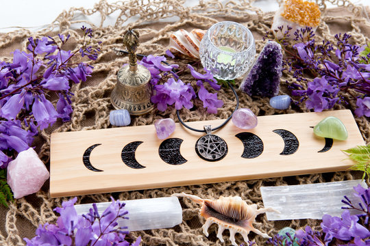 Full Moon Witch Pagan Altar decorations with Moon Phases, crystals, purple flowers and pentacle pendant