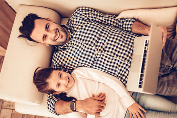 Father and Girl Lie with Laptop in Hand at Home.