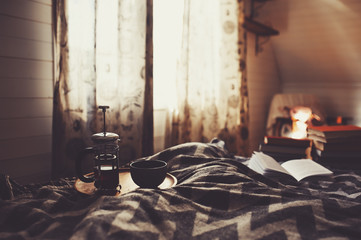 cozy winter morning with cup of hot tea. Nordic bedroom interior in country wooden house or cabin, hygge concept