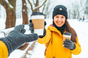 woman give cup of coffee to friend. meeting in snowed winter park