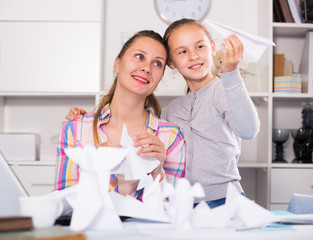 Woman and girl making airplanes of pape