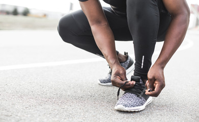 Young sportsman tying shoelaces on sport shoes. Fit, fitness, exercise, workout and healthy lifestyle concept. free space for text