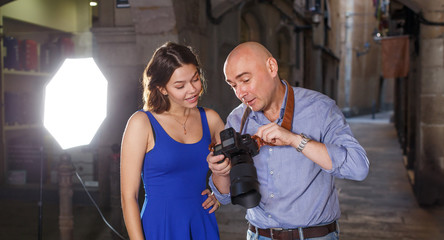 Photographer showing photos on camera to model girl