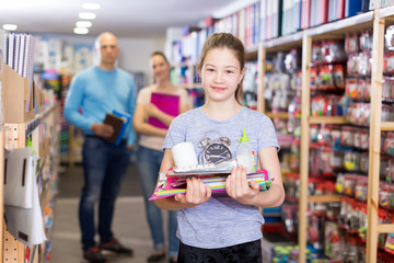 Satisfied girl with family in school accessories store