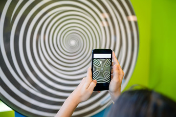 Teenage girl holding a smart phone that captures hypnotizing rotating spiral.