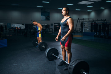 Two weightlifters doing exercise with barbells