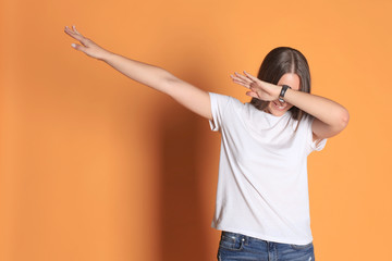 Young woman in basic clothing throws dab isolated on yellow background.