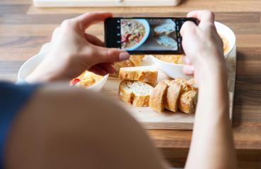 Closeup womans hands photographing vegetarian dish at health food restaurant