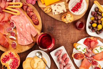 Charcuterie Tasting. A photo of many different sausages and hams, cold cuts, and a cheese platter, shot from the top on a rustic background with a glass of red wine, olives and copy space