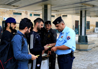 An Iraqi Policeman inspects tickets of passengers before boarding a train to Fallujah, the newly resurrected service to the city, at a railway station in Baghdad