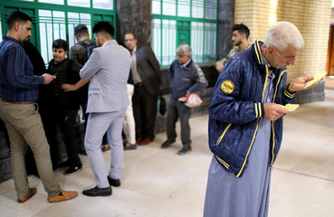A passenger checks his ticket before boarding a train to Fallujah, the newly resurrected service to the city, at a railway station in Baghdad