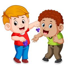 A boy is feeding his best friend with grape