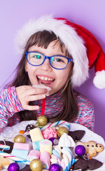 girl with santa claus hat and tray of christmas sweets