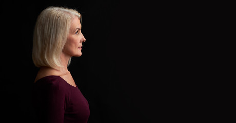 Beautiful old blonde woman profile. Isolated on black