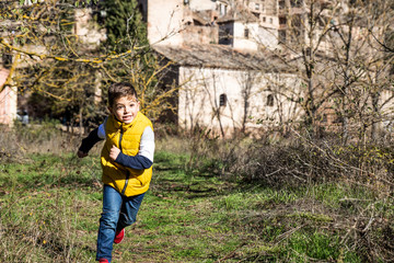 Little kid with a yellow vest running near a town