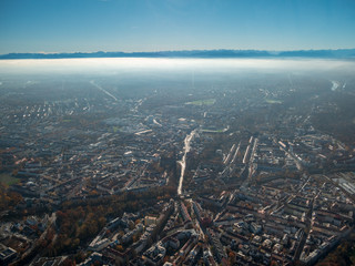 Helicopter view towards the munich and the alps toughed with fog