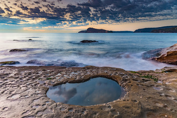 Soft Dawn Seascape with Cloud Reflections in Rock Pool