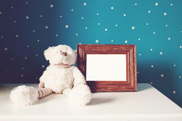 teddy bear with picture frame in nursery
