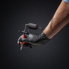 Tattooist hands in black gloves with tattoo machine on dark gray background.