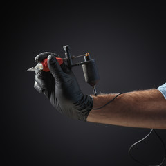 Tattooist hands in black gloves with tattoo machine on dark gray background.