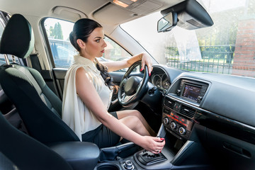 Brunette woman shifting automatic transmission lever in car