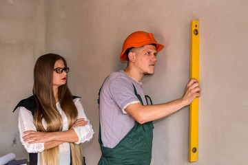 Woman controlling how man measuring wall with level tool