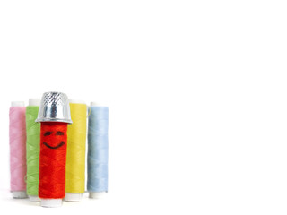 Color sewing threads. One has funny smiley face drawn on it and the thimble as a hat, viewed in close-up with copy space, isolated on white background