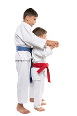 two boys in karate training, the eldest helps the younger, brothers, on a white background, isolate
