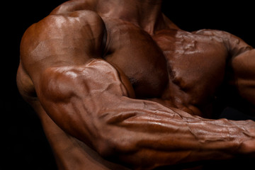 Close-up of a power fitness man's hand. Strong and handsome bodybuilder demonstrate his muscles and biceps