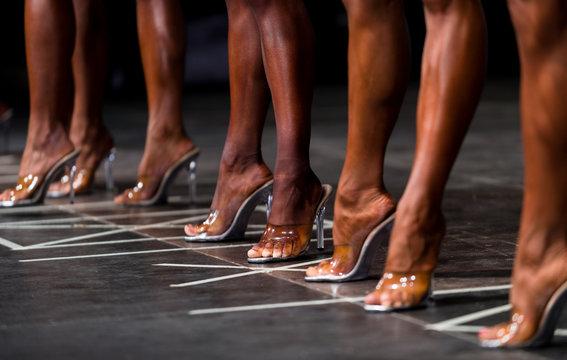 slender woman legs in high heels. women to compete in fitness bikini