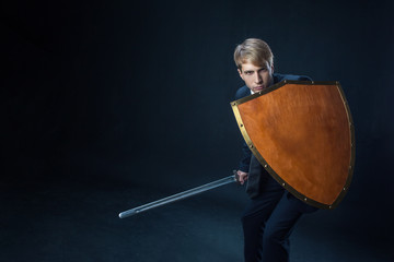 Businessman with shield and sword. Risk management and information protection concept