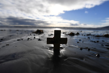 A remembrance cross is planted in the sand as volunteers drew depictions of those killed in World War One, part of Danny Boyle's Pages of The Sea celebrations, on Murlough Beach in Newcastle