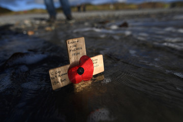 The tide washes away a remembrance cross is planted in the sand as volunteers drew depictions of those killed in World War One, part of Danny Boyle's Pages of The Sea celebrations, on Murlough Beach in Newcastle