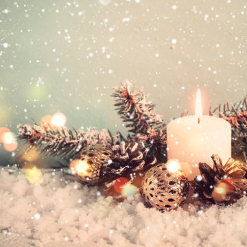 Vintage christmas greeting card. Candle and conifer on snow background