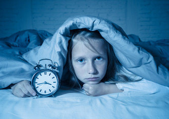 Little girl suffering from insomnia looking at alarm clock feeling desperate sad and restless