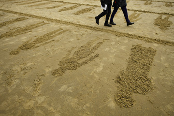 Pictures etched in the sand to commemorate those killed in World War One, part of the Pages of The Sea celebrations are seen in Folkestone