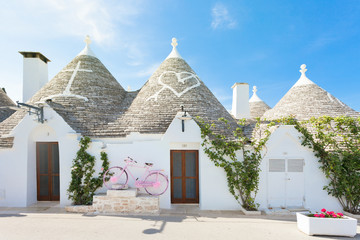 Alberobello, Apulia - A rose bicycle in front of a Trullo