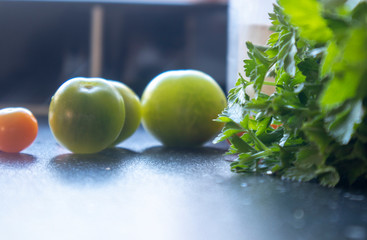 Parsley and green tomatoes, on a black kitchen worktop